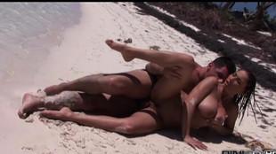 Une brune aux gros seins baise avec son mec sur une plage